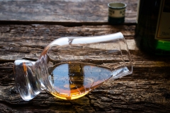 glass and bottle of whiskey on a wooden background